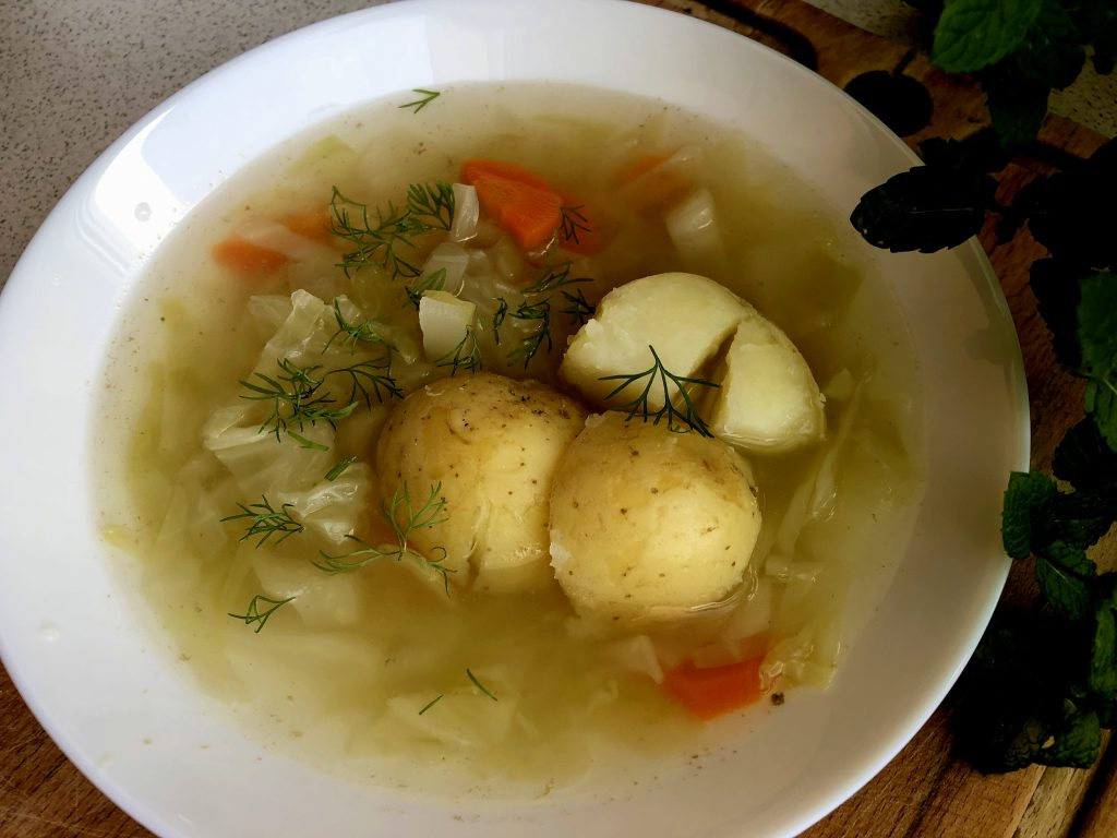 young cabbage soup on the plate with dill