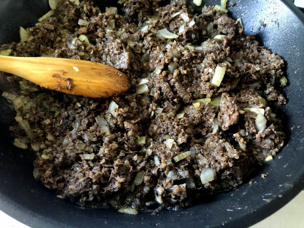 Polish kaszanka being fried on the pan with onion