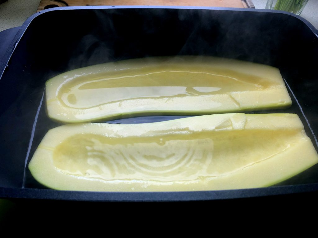 Green large zucchini peeled and covered in hot water