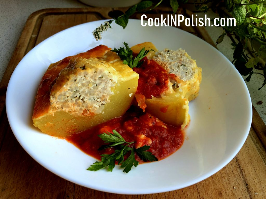 Ready baked Polish stuffed zucchini on the plate with tomato sauce.