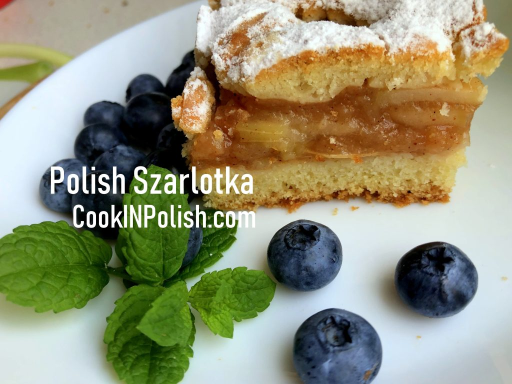 Polish apple pie served on the plate with blueberries and mint.