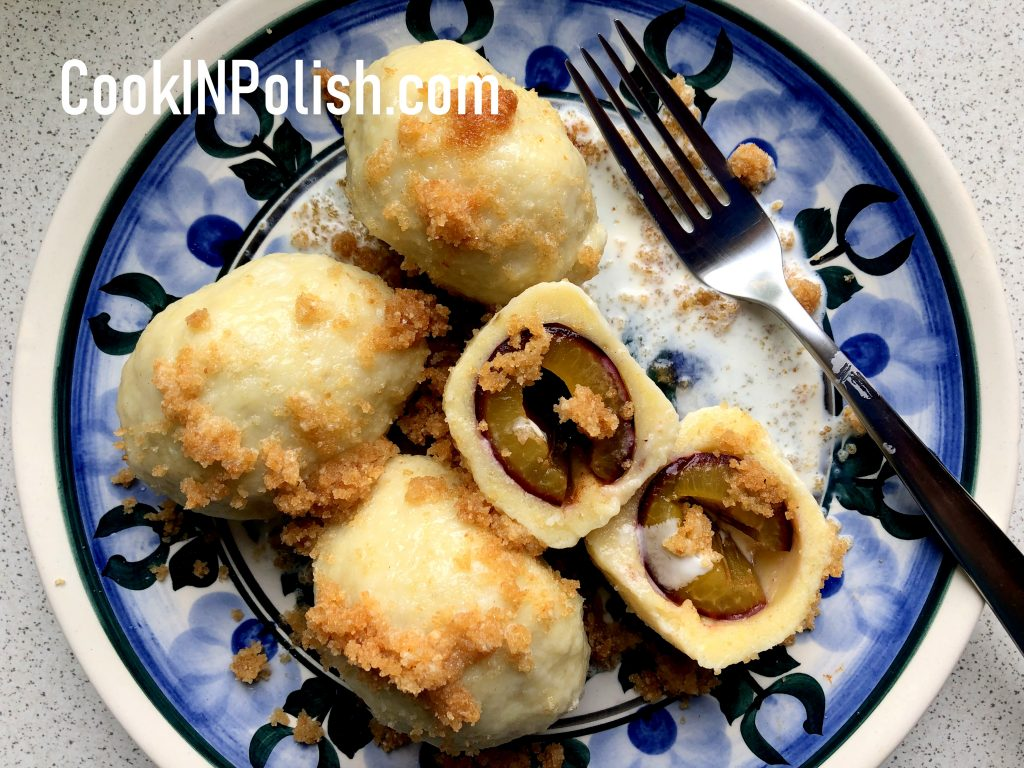 Polish Plum knedle served on the plate with breadcrumbs and sweet cream