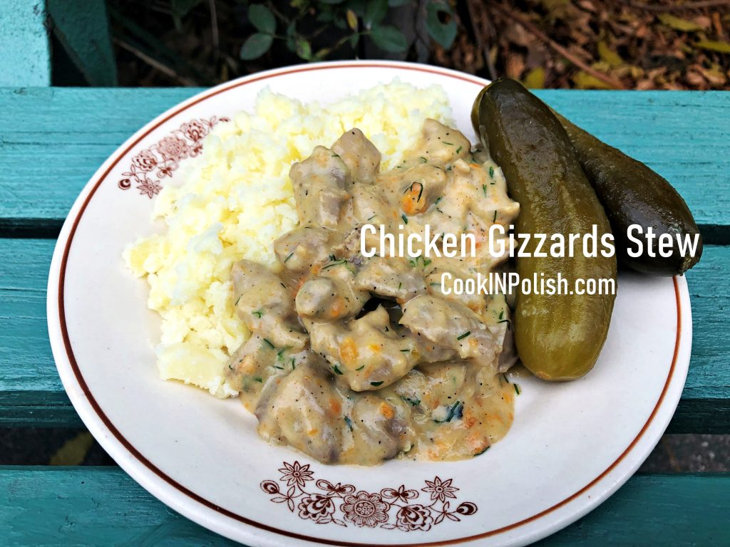 Chicken Gizzards Stew served on the plate with boiled potatoes and gherkins.