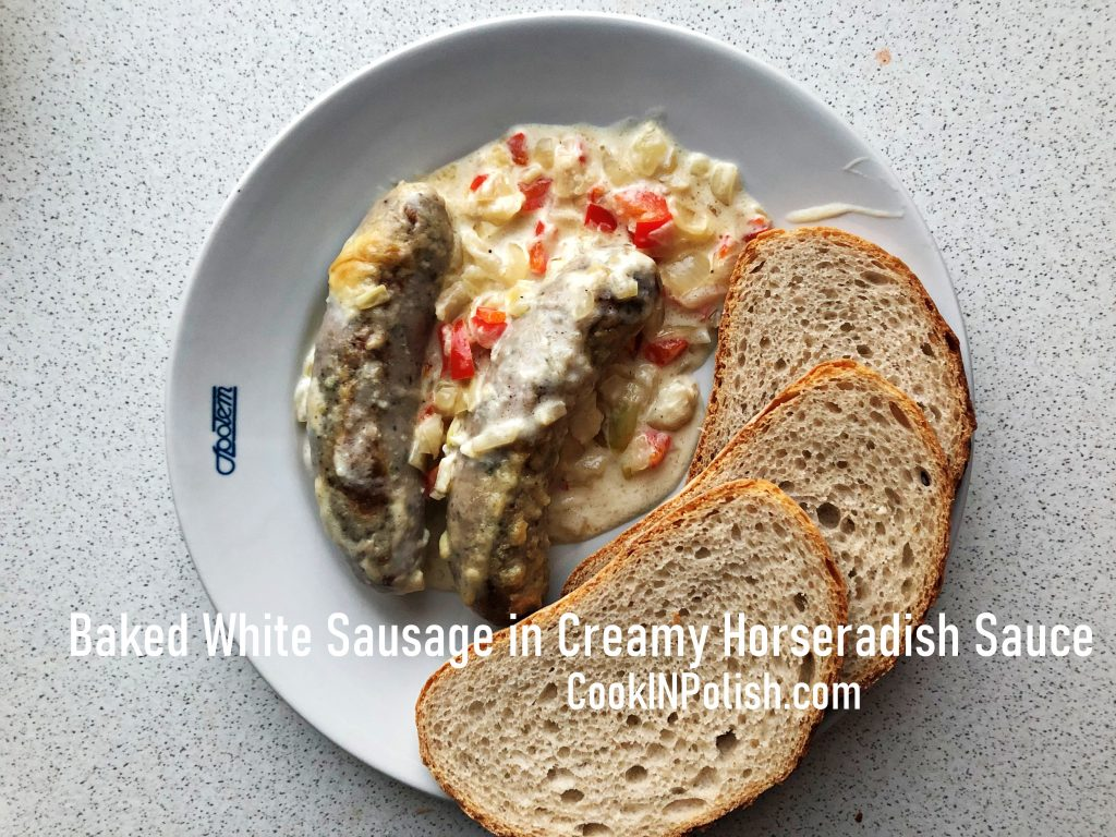 Baked white raw sausage in creamy horseradish sauce served on a plate with bread
